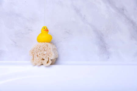 Children's hygiene products concept. Yellow duckling in the bathroom on a background of gray tiles. Copy space Archivio Fotografico