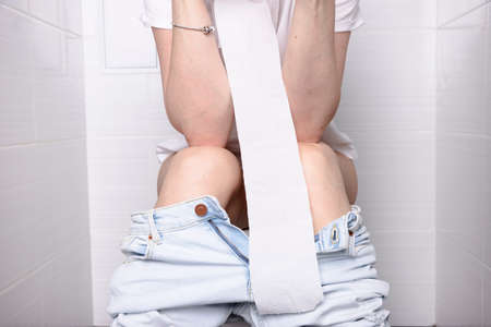 Pissing Woman, with diarrhea on a white toilet bowl in the toilet with a roll of paper in her hand.