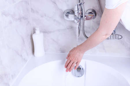 Hand washing process. Female hands under the tap with water in the bathroom.