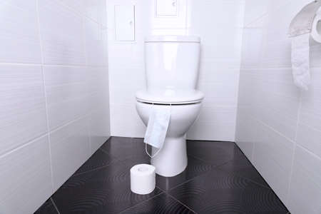 White home toilet with flush and white toilet paper and disposable medical mask in the bathroom. Quarantine concept.