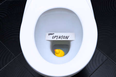 The words, the phrase YOUR OPINION is written on the note card, and the yellow duck is floating in the toilet as a reminder of the importance of customer feedback.