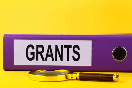 Grants, blue folder in the office on a yellow background.