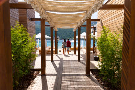 A couple walks on a wooden deck through a beach cafe to the Adriatic Sea. Montenegro, Tivat.