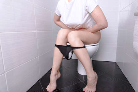 Woman pissing, with diarrhea on a white toilet bowl in the toilet with a roll of paper in her hand.
