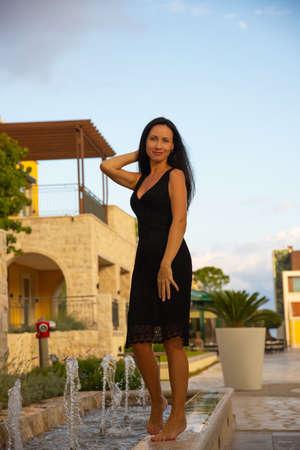Happy Caucasian beautiful woman in black summer dress walks barefoot on the fountain. Sexy fashion model. Montenegro, Tivat. Archivio Fotografico