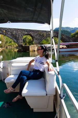 Happy caucasian beautiful woman on the pine forest of a luxury yacht. Pretty sexy fashion model. Montenegro, Lake Skadar.
