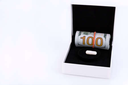 Tablet, capsule, roll of 100 dollars banknotes in a gift box. Indicator of profit from the pharmaceutical industry, the cost of tablets. Copy space. Archivio Fotografico
