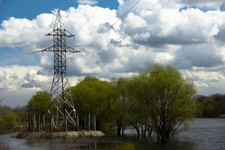 Power lines, poles and trees are flooded during the flood in the river. Archivio Fotografico