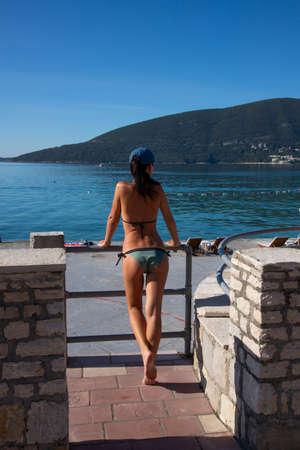 Happy caucasian beautiful woman posing on the shore of the adriatic sea. Pretty sexy fashion model. Montenegro, Tivat.