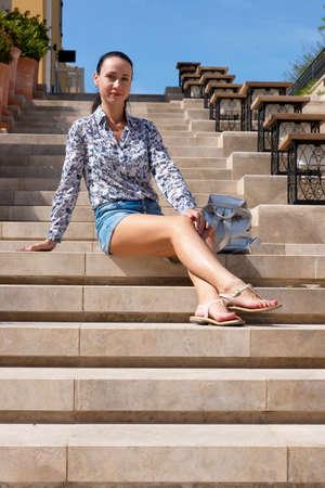 Happy caucasian beautiful woman in denim shorts by the fountain. Pretty sexy fashion model. Montenegro, Tivat.