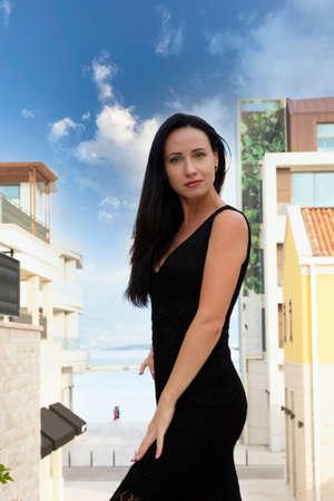 Happy Caucasian beautiful woman in black summer dress. Pretty sexy fashion model. Montenegro, Tivat. Archivio Fotografico