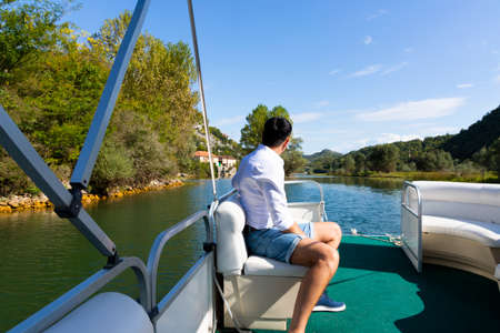 A man travels along the river among the mountains on a yacht. Montenegro, skadar lake.