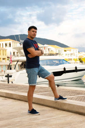 Caucasian man in a T-shirt and denim shorts posing near the yacht in the port. Tivat, Montenegro. Archivio Fotografico