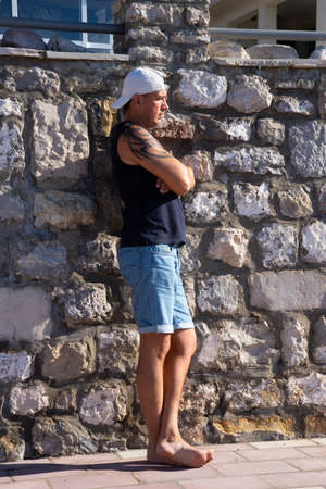 A strong and handsome young man with a tattoo on his arm posing on the old embankment. Tivat, Montenegro.