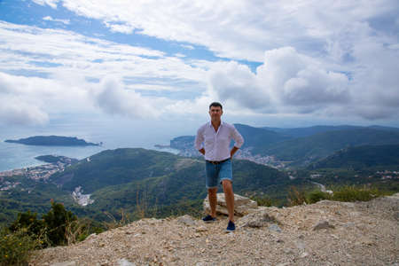 Caucasian man posing on the edge of a mountain peak with a gorgeous view of the Adriatic Sea and the city of Budva, Montenegro.