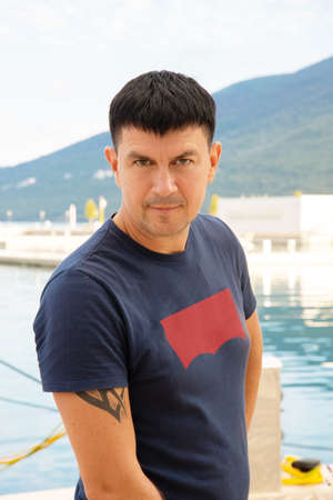Caucasian man in a blue T-shirt poses near a yacht in the port, Tivat, Montenegro.