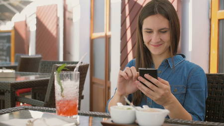 Brunette girl in a dress uses smart phone while sitting outside in a cafe, smiles and laughs. 4k,