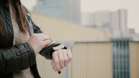 Woman in a leather jacket using her smartwatch touchscreen standing on the roof, then walks away. hands closeup. 4k