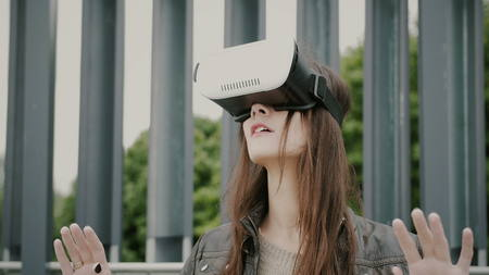 invisible: Brunette woman uses virtual reality glasses in the urban space. 4k