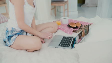 browses: Happy young woman sitting on the bed and dancing. Brunette girl uses laptop, browses the Internet during breakfast.