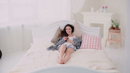 browses: Young woman using wireless technology lying on the bed and typing on touchscreen. Girl browses the Internet in morning. Stock Photo