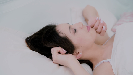 wellness sleepy: Attractive young woman waking up in bed at home. Girl looks to camera and cute smiles. Fresh and happy woman in morning. Stock Photo