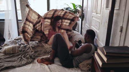 Sesión de fotos de la mañana en la cama. mujer atractiva en pijama se esconde debajo de la manta, el hombre toma la foto en la cámara pasada. Foto de archivo - 76938924