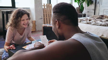 Happy multiethnic couple in pajamas playing the board game on the floor. Man throws dice and puts the card, woman laugh.