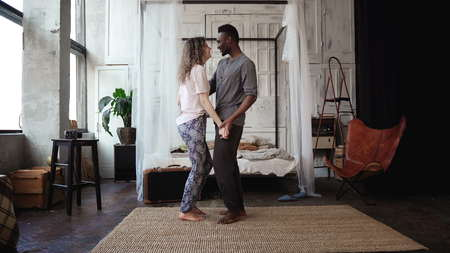 Multiethnic couple dancing in pajamas. African male and Caucasian female look happy, laughing and smiling, holding hands