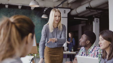 Young blonde woman manager talking with mixed race team. Businesswoman giving direction to colleagues at modern office. Stock Photo