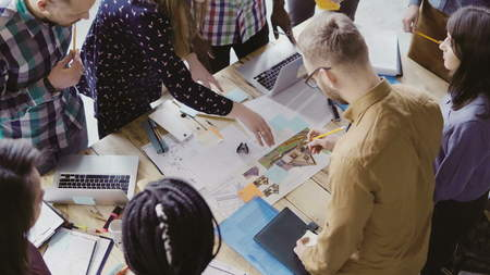 Top view of young team working on architectural project. Group of mixed race people standing near table and discussing.