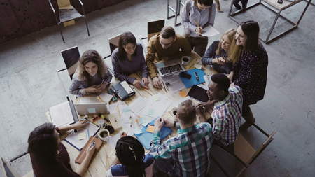 Top view of group of mixed race people sitting at table, talking and then start to clapping together. Business meeting.