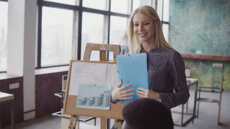 Close-up view of female manager walking through the office with documents. Multiracial team clap to businesswoman. Stock Photo