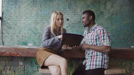 African businessman and caucasian businesswoman sitting at modern trendy office, looking at documents together.