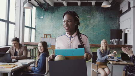 Young african woman recently hired for corporate job comes into new office. Female holds box with personal belongings. Stock Photo