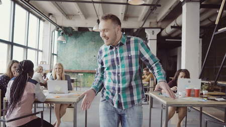 Happy businessman walking through the modern office and doing crazy dance. Man in cheerful mood greets with colleagues.