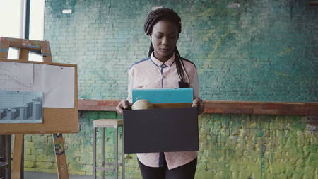 Young african woman getting fired from work. Female walks through the office, carrying box with personal belongings. Stock Photo