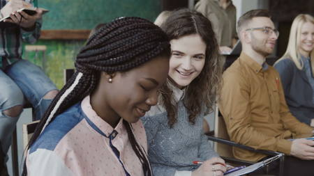 Young creative business team in conference at modern office. Two colleagues, african and caucasian woman talking. Stock Photo