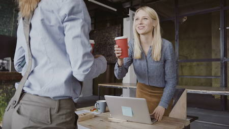 Brunette female manager comes to modern office at work. Young woman greets with colleagues, brings coffee to friend. Stock Photo