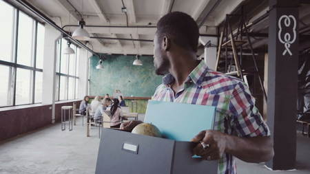 Young african man get fired from work at start-up. Male walks through the office, carrying box with personal belongings.