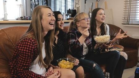 Beautiful girlriends watch soap on TV. Girls smile and laugh enjoying emotional romantic movie 4K slow motion. Banco de Imagens - 103162650