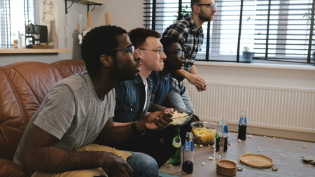 Mixed race male supporters watch sports on TV. Fans celebrate goal victory holding British flag cushion. Slow motion.