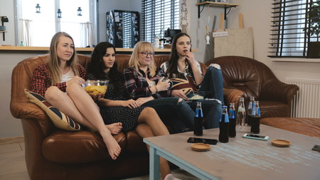 Female friends watch sad movie on TV at home. Young beautiful European girls watching romantic emotion film comedy 4K.