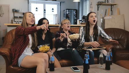 Female friends watch TV show with snacks at home. Young European girls enjoying romantic comedy slow motion 4K.