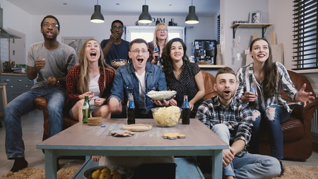 Diverse group of friends watching sports on TV Football supporters celebrate success with popcorn and drinks. Emotion 4K Stock Photo