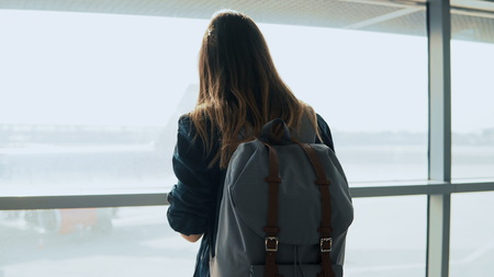 Young girl using smartphone near airport window. Happy European woman with backpack uses mobile app in terminal. Stock Photo