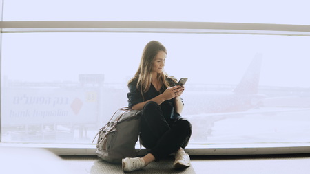 Happy woman sits with smartphone by airport window. Caucasian girl with backpack using messenger app in terminal. 4K.