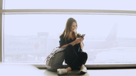 Happy woman sits with smartphone by airport window. Caucasian girl with backpack using messenger app in terminal.