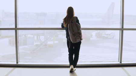 Young woman with backpack near terminal window. Caucasian female tourist using smartphone in airport lounge. Travel. 4K. Stok Fotoğraf