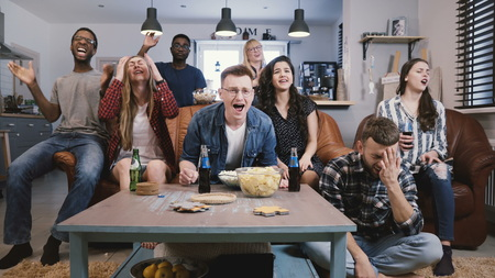Diverse group get upset watching sports on TV. Football fans sad and emotional. Supporters sit cheering together. 4K Stock Photo